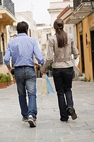 Back side of couple with shopping bags