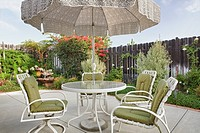 hard landscaping, a paved patio in a garden. Tables and chairs. Umbrella, shade. Plants, flowering shrubs in a border. Water feature. High fence. Furn...