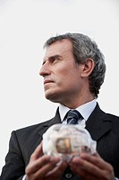 Mature man holding transparent piggy bank filled with euros