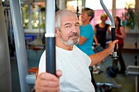 Elderly man working out on butterfly machine in gym