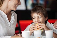 Boy eating hamburger in fast food restaurant