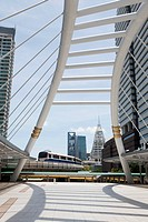A mass transit train on an elevated track passes modern buildings in the central business district of Bangkok. Public transport. A passenger bridge an...
