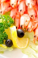 Lemon and black olives with shrimps soft focus