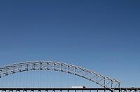 I_64 road bridge across a river. A steel arch construction against a blue sky. A freight container truck, a Semi_truck crossing bridge. Louisville, Ke...