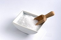 Isoltaed bowl with salt in it and a wooden spoon.