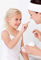 Mother and daughter in the bathroom putting cream on face
