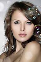 Portrait of a young woman surrounded by soap bubbles