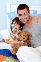 Father and son playing doctors in bed with a teddy bear