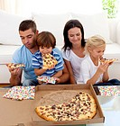 Happy family eating pizza in living_room all together