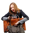 Young businesswoman with suitcase and handbag and looking at her cellphone