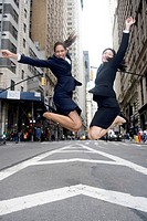 A mixed race African American and an Asian business women jump for joy in an outdoor urban setting.