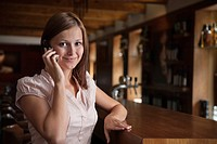 portrait of young woman at bar talking on mobile phone