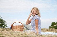 young woman talking on mobile phone in field