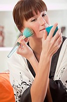 young woman in bathrobe holding make up brush