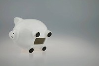 White Piggy bank on its side with Coin slot open showing piggy bank empty