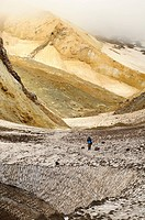 hiker walking through canyon with sulphur sediments in Mutnovsky volcano area on Kamchatka