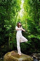 Female meditating in tropical rainforest, standing on a boulder.