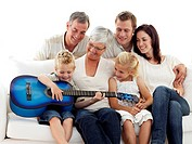 Happy grandparents, parents and children playing guitar at home