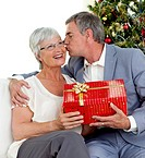 Senior man giving a kiss and a Christmas present to his wife at home