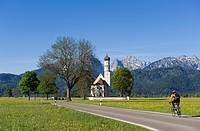 Cyclist on the road to the pilgrimage church of St. Coloman, Schwangau near Fuessen, Bavarian Alps, Allgaeu, Upper Bavaria, Bavaria, Germany, Europe