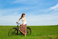 Young woman with a vintage bicycle on a green meadow