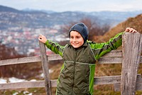 Little boy sitting on a wooden fence in the countryside