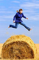 girl jumping up on straw roll