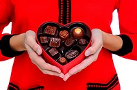 Woman wearing red sweater holding a Box Heart of Valentines Day Candy in front of her torso. Close shot in horizontal format.