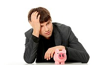 Depressed businessman with piggybank. Isolated on white