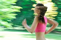 Young person woman running outside in park on sunny day _ motion blurr