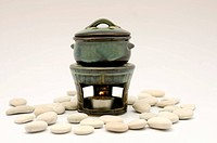 A green_and_black clay aromatherapy burner on a stand, surrounded by smooth river pebbles.