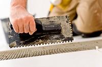 Home improvement, renovation _ handyman laying tile, trowel with mortar
