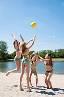 Group of girls playing with a ball on the beach of a lake