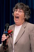 Elderly woman singing into microphone