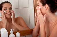 Young woman applying cream in the bathroom