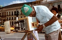 Photographer using ancient handmade camera to photograph people on the steps of the Capitolio, Havana, Cuba, He uses paper for the negative and rephot...