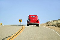 A restored bright Red pickup truck, mid-30's, drives rural highway in Kern County near Lockwood Valley, CA
