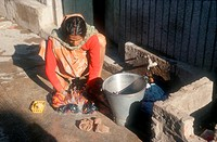 Woman crouching in street beside roadside tap washing clothes ,