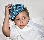 sick little boy in bed with ice bag on his head