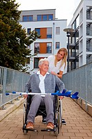 Happy woman in wheelchair with nurse on a ramp