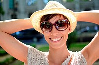 Attractive young woman with summer style and straw hat in street