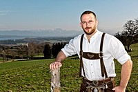A handsome bavarian man standing in front of the Alps