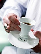 Person holding a cup of coffee with Love written on the saucer