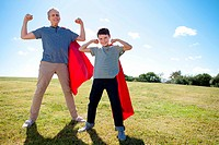 Grandfather and grandson wearing superhero capes flexing muscles