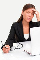 Headache and Stress at work. Young professional woman stressed and tired with headache sitting at office desk. Shallow depth of field, focus on glasse...