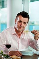 Businessman eating noodles, portrait