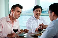 Multi racial businesspeople eating meal