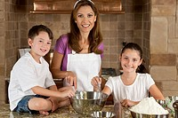 An smiling mother, daughter and son family cooking and baking chocolate chip cookies in a kitchen at home