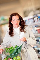 Young woman buying shampoo and holding shopping basket