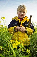 Young boy wearing a rain coat, standing in a field of mustard seeds